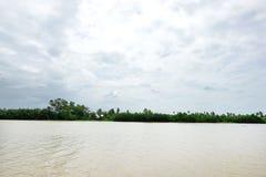 在Chachoengsao猛击有天空、云彩和树的Pakong河在泰国 免版税库存图片