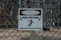 在Chainlink的退色的高压危险标志 库存照片