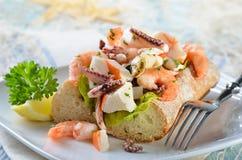 在ciabatta面包的海鲜沙拉 免版税图库摄影