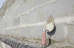 在cinderblock灰色背景的修平刀 以砖砌为背景是修平刀 免版税库存照片