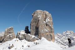 在Cinque Torri峰顶前面的滑雪者 免版税库存照片