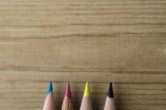 在CMYK颜色的铅笔行在木背景 库存图片