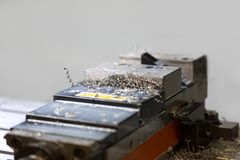 在CNC机器里面的绑制钳持有人有金属芯片的 库存照片