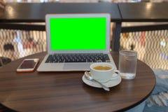 在Cofee商店喝咖啡和与在桌上的labtop一起使用在咖啡店精选的焦点,使用他的膝上型计算机的特写镜头,膝上型计算机gre 库存图片