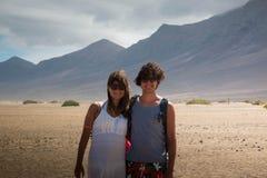 在Cofete海滩,费埃特文图拉岛的愉快的夫妇 中景有风景背景 图库摄影
