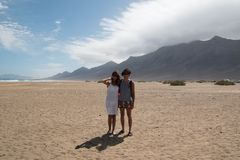 在Cofete海滩,费埃特文图拉岛的愉快的夫妇 宽射击有风景背景 库存图片