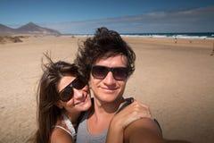 在Cofete海滩,费埃特文图拉岛的愉快的夫妇 selfie有风景背景 库存照片