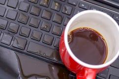 在coffe下落看法和一个红色杯子在膝上型计算机的coffe上,损坏液体弄湿并且溢出在键盘,事故 库存图片