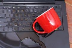 在coffe下落看法和一个红色杯子在膝上型计算机的coffe上,损坏液体弄湿并且溢出在键盘,事故 免版税库存照片