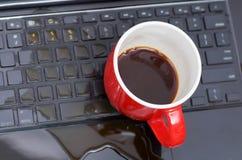 在coffe下落看法和一个红色杯子在膝上型计算机的coffe上,损坏液体弄湿并且溢出在键盘,事故 免版税库存图片