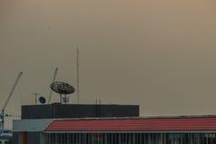 在condomin的水泥甲板上面屋顶地板上的卫星盘 免版税库存照片