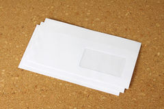 在corkboard背景的白色信封。 免版税库存照片