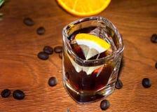 在cristal玻璃的酒精鸡尾酒与柠檬切片和咖啡豆 免版税图库摄影