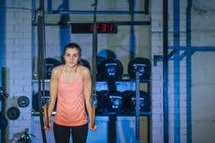 在crossfit圆环的锻炼 健身在TRX的妇女锻炼在健身房 E 健身 免版税库存图片