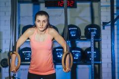 在crossfit圆环的锻炼 健身在TRX的妇女锻炼在健身房 E 健身 免版税图库摄影
