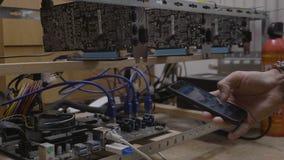 在cryptocurrency开采的船具连接的智能手机的矿工工程师年轻人观看的开采的软件过程- 股票视频