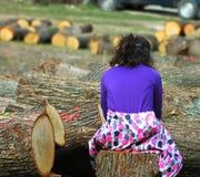 在cutted树之间的少女 免版税库存图片