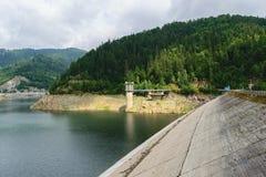 在Dambovita河的Pecingeanu水坝 储积湖、入口塔和绿色森林背景 免版税库存照片