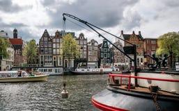 在Damrak运河的巡航游船在日落的阿姆斯特丹 免版税库存照片