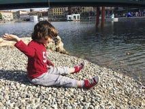 在Darsena的儿童投掷的石头在米兰在春天 免版税库存照片