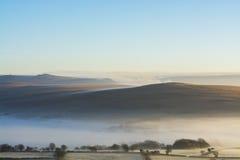 在Dartmoor的日出与滚动在小山的突岩视线内和薄雾 库存图片