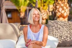 在deckchair的白肤金发的妇女选址,享受暑假 免版税库存照片