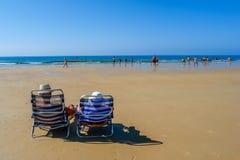 在deckchairs的夫妇坐海滩 免版税库存照片