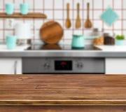 在defocused现代厨房背景的木纹理桌 图库摄影