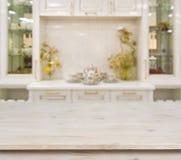 在defocused白色厨房家具背景的被漂白的木桌 图库摄影