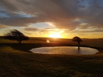 在Ditchling烽火台露水池塘的冬天日出 库存照片