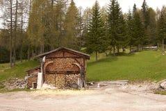 在Dolomiti山的堆木材的棚 库存图片
