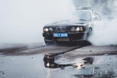 在driftshow的警车BMW 5系列灼烧的轮胎 免版税库存图片