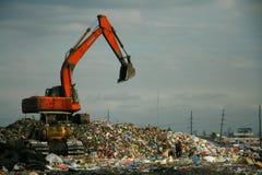 在dumpsite的红色挖掘机 库存照片