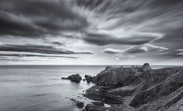 在Dunnottar城堡的日落在黑色的苏格兰海岸云彩 免版税库存图片