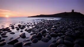 在Dunstanburgh城堡附近的海岸 库存图片