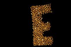 在E上写字写用荞麦在黑背景 免版税库存照片