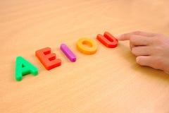 在e-i o和u上写字用儿童手,学校 库存照片