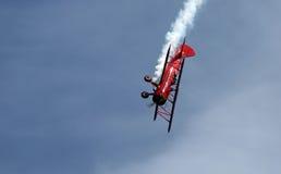 在EAA AirVenture Airshow的红色双翼飞机特技飞行 免版税库存照片