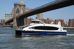 在East河的纽约渡轮在布鲁克林大桥下 库存图片