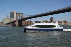 在East河的纽约渡轮在布鲁克林大桥下 免版税库存图片