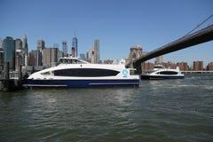 在East河的纽约渡轮在布鲁克林大桥下 免版税图库摄影