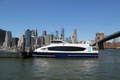 在East河的纽约渡轮在布鲁克林大桥下 图库摄影