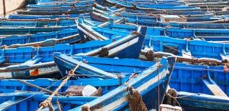 在eath旁边被栓的许多蓝色空的渔船 免版税库存照片