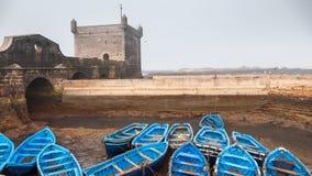 在eath旁边被栓的许多蓝色空的渔船 库存照片