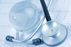 在ECG背景的听诊器和玻璃地球  免版税库存图片