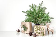 在Eco样式的圣诞节构成 在花瓶和礼物的云杉的分支在内部的桌上 模板为 免版税库存照片