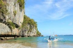 在El Nido,巴拉望岛的热带海滩,有一条tipical Philippinos小船的一个小船人的 免版税库存照片