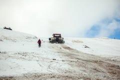 在Elbrus积雪的倾斜的红色ratrak  免版税库存图片