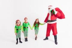 在Elven服装和孩子穿戴的圣诞老人 冰少许晚上北部企鹅极 库存照片
