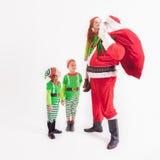 在Elven服装和孩子穿戴的圣诞老人 冰少许晚上北部企鹅极 免版税库存图片